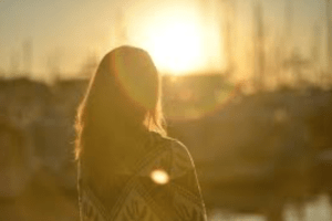 woman in front of sun