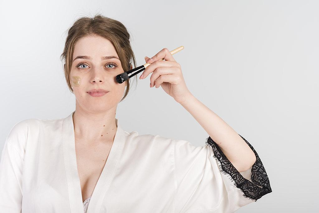 Girl applying makeup on her face