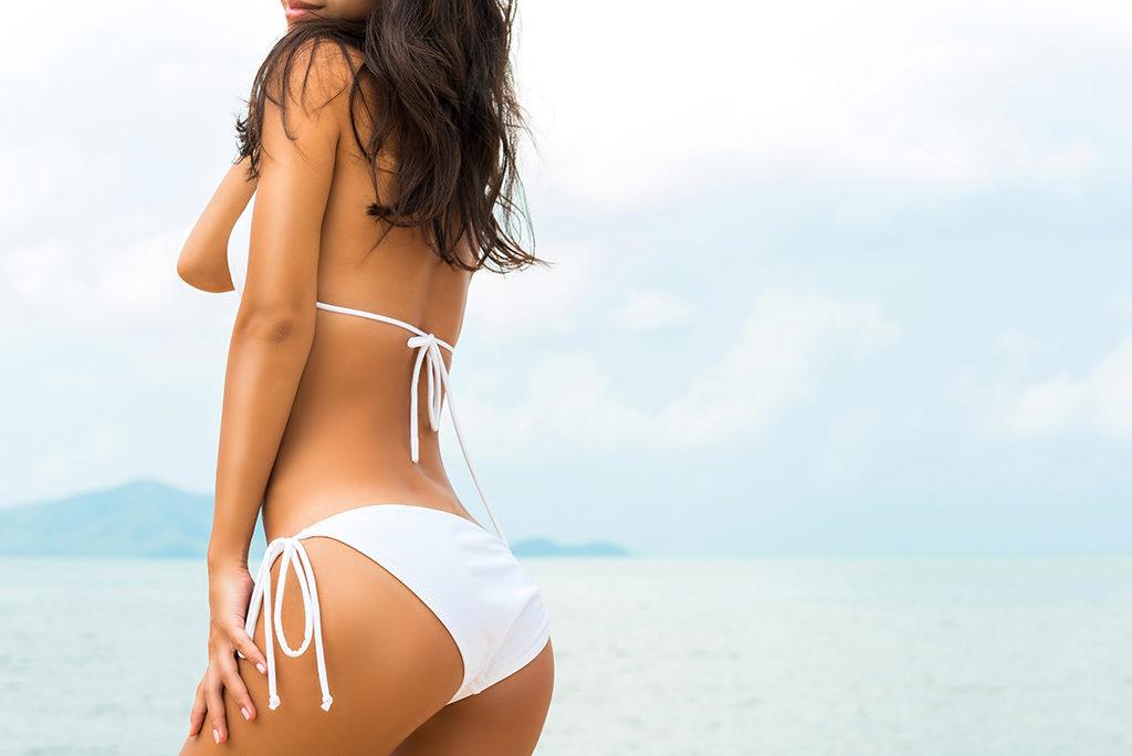 Young beautiful shape tan skin woman wearing white bikini swimsuit posing at the beach in summer, back view