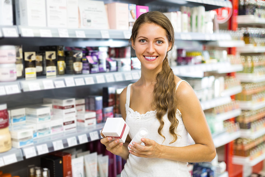 Young girl choosing cream for herself in the shop