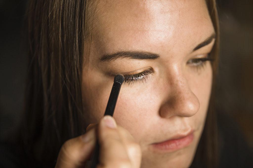 portrait-beautiful-young-woman-applying-eye-shadow